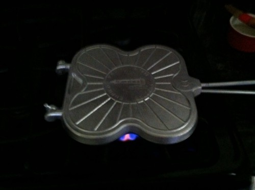 Tigelle iron heating over a gas stove